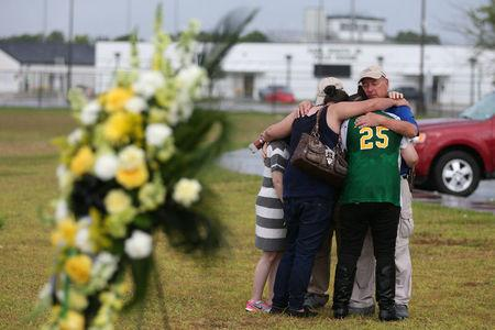 People mourn at a makeshift memorial left in memory of the victims killed in a shooting at Santa Fe High School in Santa Fe Texas U.S