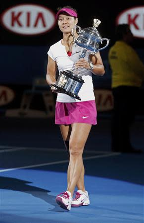 Li Na of China walks with the Daphne Akhurst Memorial Cup after defeating Dominika Cibulkova of Slovakia in their women's singles final match at the Australian Open 2014 tennis tournament in Melbourne January 25, 2014. REUTERS/Bobby Yip
