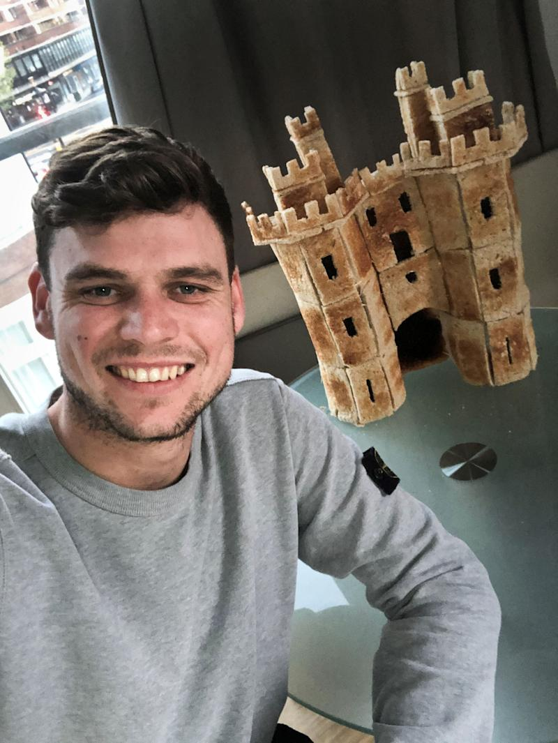 PIC BY MATTY CLOSE / CATERS NEWS - (PICTURED: Matty Close from Lancaster with a toast replica of Lancaster Castle made of toast. Pic Taken 11/04/2020 ) - A bored man decided to spend his time in isolation creatively and made a castle out of toast bread. Matt Close,30, who works in constructions, originally from Lancaster but lives in London celebrated his birthday on the 11th of April (SAT) having some drinks alone.After waking up slightly hungover, he came up with the idea of creating something and having no supplies, he used toast bread and cocktail sticks to create a replica of the Castle in his hometown, Lancaster. The toasty castle that is made of two and a half loaves of bread, is almost 2ft high and over 4 ft wide, took over five hours to complete. - SEE CATERS COPY