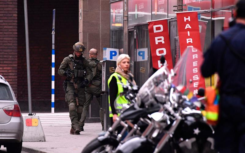 Armed police on the streets of Stockholm - Credit: Police officers at the scene of the Stockholm attack/AFP