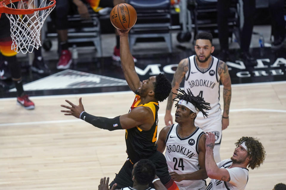 Utah Jazz guard Donovan Mitchell goes to the basket as Brooklyn Nets' Alize Johnson (24) and Tyler Johnson, right, defend during the first half of an NBA basketball game Wednesday, March 24, 2021, in Salt Lake City. (AP Photo/Rick Bowmer)