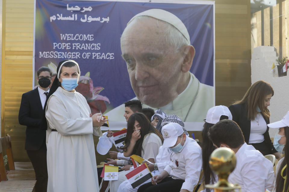 Faithful wait outside the Chaldean Cathedral of Saint Joseph where Pope Francis is expected to concelebrate mass in, in Baghdad, Iraq, Saturday, March 6, 2021. Earlier today Francis met privately with the country's revered Shiite leader, Grand Ayatollah Ali al-Sistani. (AP Photo/Andrew Medichini)