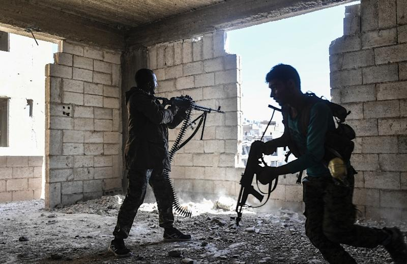 Members of the Syrian Democratic Forces fire their weapons during a battle against Islamic State group jihadists in Raqa on September 28 (AFP Photo/BULENT KILIC)