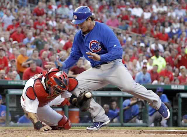 Chicago Cubs' Anthony Rizzo, right, is safe at home while colliding with St. Louis Cardinals catcher Yadier Molina during the second inning of a baseball game on Wednesday, June 19, 2013, in St. Louis. The ball popped out of Molina's glove on the play. (AP Photo/Jeff Roberson)