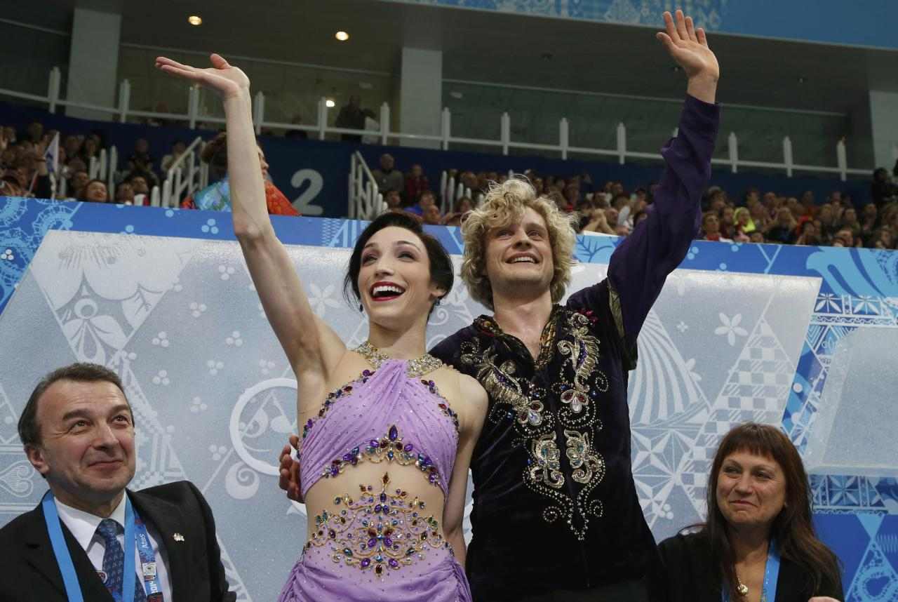"Meryl Davis and Charlie White of the U.S. wave at the ""kiss and cry"" area after their figure skating ice dance free dance program at the Sochi 2014 Winter Olympics, February 17, 2014. REUTERS/Lucy Nicholson (RUSSIA - Tags: SPORT FIGURE SKATING OLYMPICS)"
