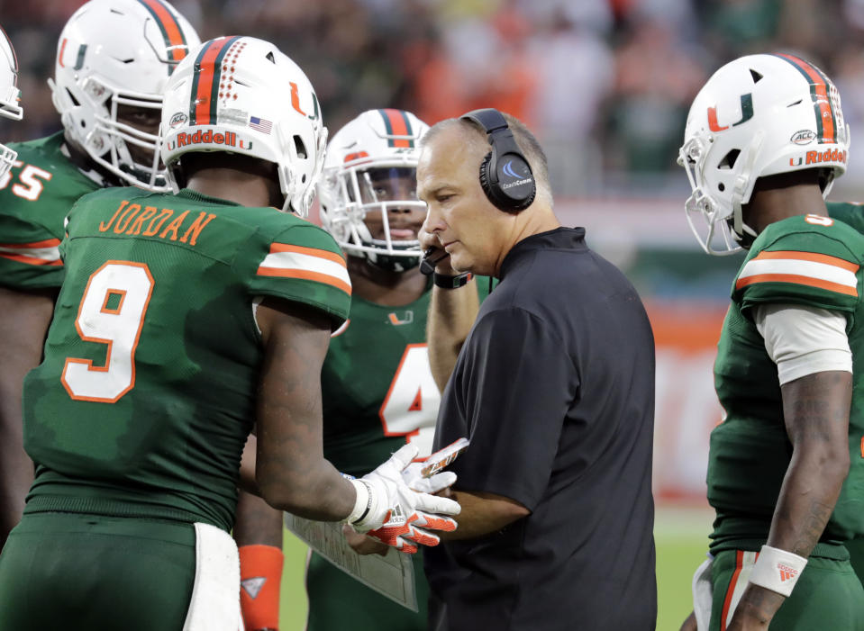 FILE - In this Saturday, Oct. 6, 2018, file photo, Miami head coach Mark Richt, center, talks with tight end Brevin Jordan (9) during the second half of an NCAA college football game against Florida State, in Miami Gardens, Fla. Former Georgia and Miami football coach Richt has been diagnosed with Parkinson's disease. Richt, who guided the Bulldogs for 15 seasons and closed out his coaching career at alma mater Miami, made the announcement Thursday, July 1, 2021, on Twitter. (AP Photo/Lynne Sladky, File)