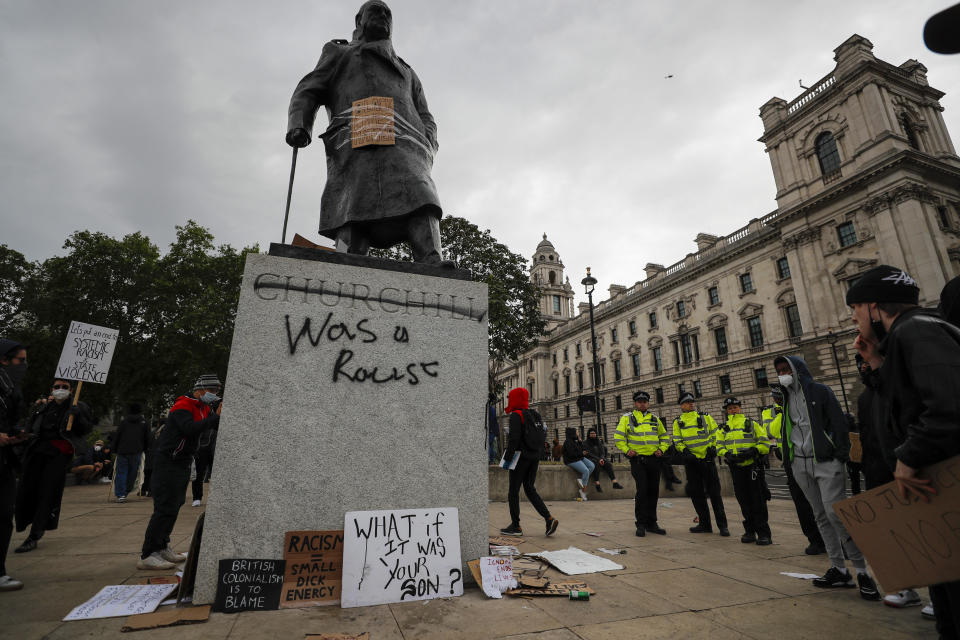 Protesters and police gather around Winston Churchill statue in Parliament Square during the Black Lives Matter protest rally in London, Sunday, June 7, 2020, in response to the recent killing of George Floyd by police officers in Minneapolis, USA, that has led to protests in many countries and across the US. (AP Photo/Frank Augstein)