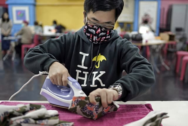 A volunteer irons a handmade cotton mask (Kin Cheung/AP)
