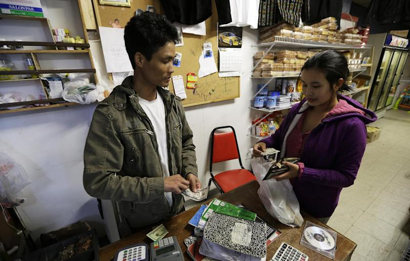 Ngun Za Bik, left, helps a customer at the front counter of his Grace Chin Store in Columbus Junction, Iowa on Wednesday, April 17, 2013. Tyson Food's decision to recruit Burmese refugees marks a new chapter in this southeast Iowa meatpacking town which had previously brought in Mexicans, Hondurans and El Salvadorans. (AP Photo/Charlie Neibergall)