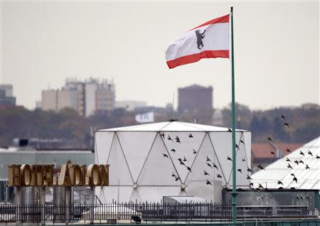 Birds fly beside a white covered structure and a Berlin city flag next to the roof of the British embassy in Berlin