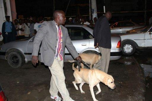 Kenyan police officers arrive with sniffer dogs at the scene of a grenade attack in Mombasa