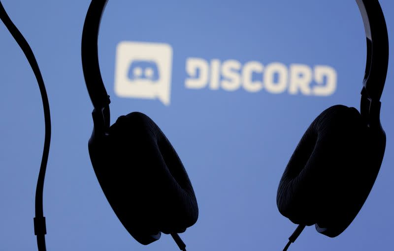 Headphones are seen in front of displayed Discord app logo in this illustration photo