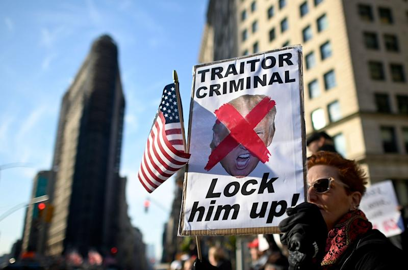 A protester holding a sign reading 'Traitor, Criminal, Lock him up!' close to where President Donald Trump is giving a speech at Madison Square Park in New York City to mark Veterans Day: AFP via Getty Images