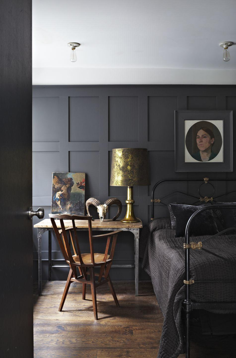 """<p>For a dramatic grey bedroom, paint panelling in deep grey to create a warm and cocooning feel. The stunning lamp and brass details on the black metal bed set it off perfectly and add shine, adding to the cosy feel. A traditional dark oak floor adds warmth and gives an aura of permanence. Painting the picture frame in the same colour as the wall means the image stands out.</p><p>Top Tip: If you don't have panelling, fake it with wallpaper - for example, this <a href=""""https://go.redirectingat.com?id=127X1599956&url=https%3A%2F%2Fwww.ilovewallpaper.co.uk%2Fwallpaper-c1%2Fcontemporary-wood-panel-wallpaper-soft-grey-p8002%2Fs8153&sref=https%3A%2F%2Fwww.housebeautiful.com%2Fuk%2Fdecorate%2Fbedroom%2Fg35432015%2Fgrey-bedroom-ideas%2F"""" rel=""""nofollow noopener"""" target=""""_blank"""" data-ylk=""""slk:Contemporary Wood Panel Wallpaper from I Love Wallpaper"""" class=""""link rapid-noclick-resp"""">Contemporary Wood Panel Wallpaper from I Love Wallpaper</a> or this beautiful <a href=""""https://go.redirectingat.com?id=127X1599956&url=https%3A%2F%2Fwww.worldofwallpaper.com%2Fimitations-marble-wood-panel-effect-wallpaper-teal-erismann-6319-18.html&sref=https%3A%2F%2Fwww.housebeautiful.com%2Fuk%2Fdecorate%2Fbedroom%2Fg35432015%2Fgrey-bedroom-ideas%2F"""" rel=""""nofollow noopener"""" target=""""_blank"""" data-ylk=""""slk:Marble Wood Panel Effect Wallpaper from World of Wallpaper"""" class=""""link rapid-noclick-resp"""">Marble Wood Panel Effect Wallpaper from World of Wallpaper</a>.</p><p>Pictured: <a href=""""https://go.redirectingat.com?id=127X1599956&url=https%3A%2F%2Fwww.farrow-ball.com%2Fen-gb%2Fpaint-colours%2Frailings%3Fsku%3D5051836127312&sref=https%3A%2F%2Fwww.housebeautiful.com%2Fuk%2Fdecorate%2Fbedroom%2Fg35432015%2Fgrey-bedroom-ideas%2F"""" rel=""""nofollow noopener"""" target=""""_blank"""" data-ylk=""""slk:Railings Modern Eggshell, Farrow & Ball"""" class=""""link rapid-noclick-resp"""">Railings Modern Eggshell, Farrow & Ball</a></p>"""