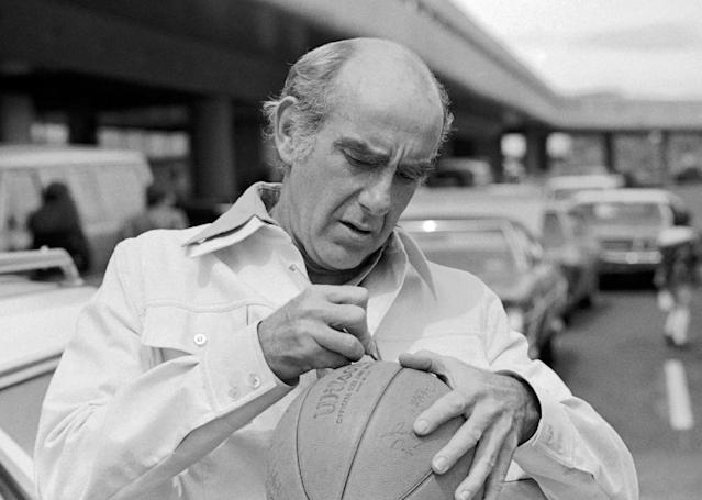 FILE - In this Friday, May 28, 1977, file photo, Portland Trail Blazers head coach Jack Ramsay autographs a basketball as the team arrived in Portland, Ore., as the trail Blazers trail the Philadelphia 76ers two games to none in their best of seven series for the NBA basketball title. Ramsay, a Hall of Fame coach who led the Portland Trail Blazers to the 1977 NBA championship before he became one of the league's most respected broadcasters, has died following a long battle with cancer. He was 89. (AP Photo/File)