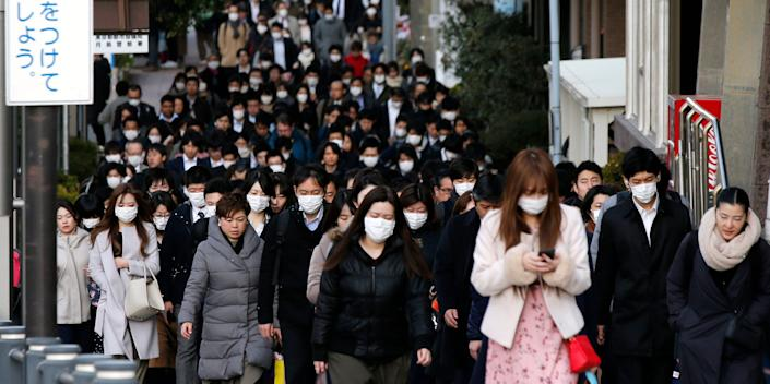 People wear masks as they commute during the morning rush hour in Chuo district in Tokyo.