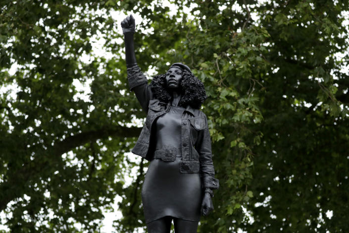"""A new black resin and steel statue entitled """"A Surge of Power (Jen Reid) 2020"""" by artist Marc Quinn stands after the statue was put up this morning on the empty plinth of the toppled statue of 17th century slave trader Edward Colston, which was pulled down during a Black Lives Matter protest in Bristol, England, Wednesday, July 15, 2020. On June 7 anti-racism demonstrators pulled the 18-foot (5.5 meter) bronze likeness of Colston down, dragged it to the nearby harbor and dumped it in the River Avon — sparking both delight and dismay in Britain and beyond. (AP Photo/Matt Dunham)"""