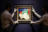 Gallery assistants hold artwork titled 'Femme nue couchee au collier' by painter Pablo Picasso during a photocall at Christie's auction house, in London