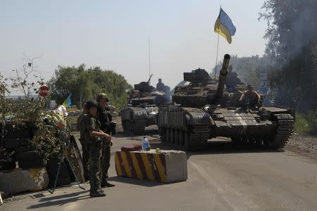 Ukrainian army tanks move past a checkpoint as they patrol area near eastern Ukrainian town of Debaltseve