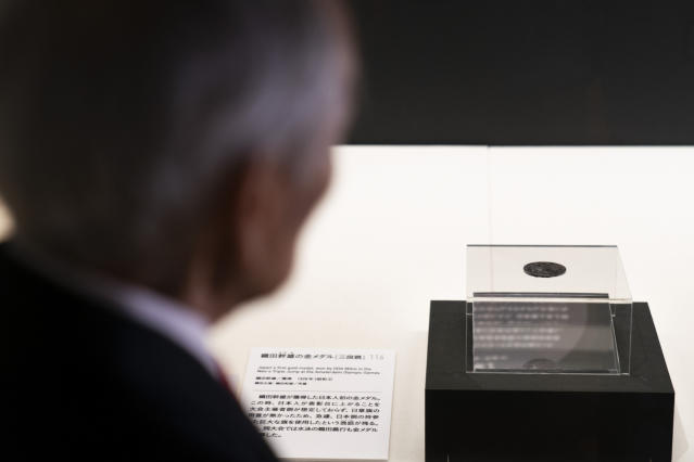In this July 8, 2019, photo, Kazuo Oda, a son of Mikio Oda, who won Japan's first Olympic gold medal and Asia's first individual gold medal at the 1928 Amsterdam Olympics, looks at his father's gold medal on display at Edo-Tokyo Museum in Tokyo. (AP Photo/Jae C. Hong)