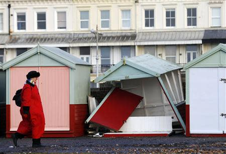 A woman walks past a beach hut destroyed by recent storms on the promenade at Brighton in southern England January 7, 2014. REUTERS/Luke MacGregor