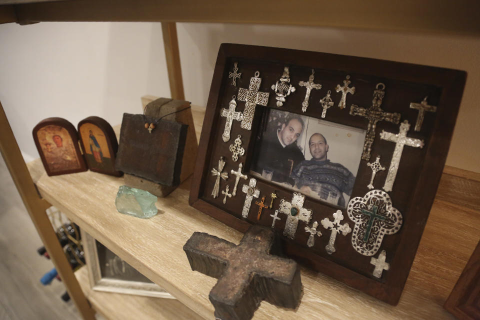 A photo of Anthoula Katsimatides' brothers John, left, and Michael Katsimatides, right, who died just one year apart from each other, sits on a shelf beside a cross fashioned from the steel of the fallen World Trade Center on Monday, Aug. 30, 2021, in the Queens borough of New York. John often visited the old St. Nicholas Greek Orthodox Church to say a prayer and light a candle as he went to or from work nearby on the 104th floor of the World Trade Center's north tower. The church stood as a quiet oasis amid the soaring financial district. (AP Photo/Jessie Wardarski)