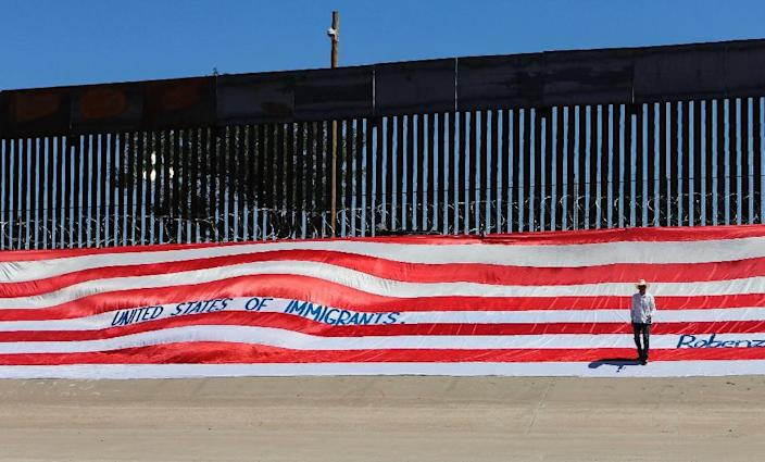 Roberto Marquez, a Mexican resident of the United States, places a flag with the message 'United States of Immigrants' on the border wall next to the Rio Grande River near El Paso (AFP Photo/HERIKA MARTINEZ)