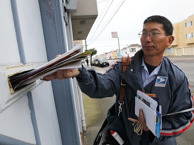 US Postal Service lettercarrier Raymond Hou delivers mail along his route: Getty Images
