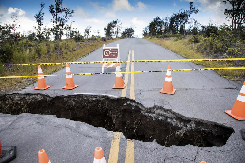 This photo provided by the National Park Service shows a large sinkhole at the Kilauea Overlook intersection inside Hawaii Volcanoes National Park in Hawaii on Friday, Aug. 17, 2018. Slowing activity at Hawaii's Kilauea volcano is prompting scientists to downgrade their alert level for the mountain. (Janice Wei/National Park Service via AP