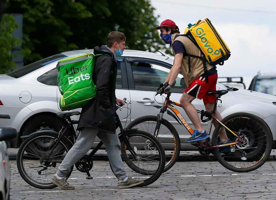 Uber Eats and Glovo delivery couriers with bicycles cross a street amid the outbreak of the coronavirus disease (COVID-19) in central Kiev, Ukraine May 13, 2020. REUTERS/Gleb Garanich