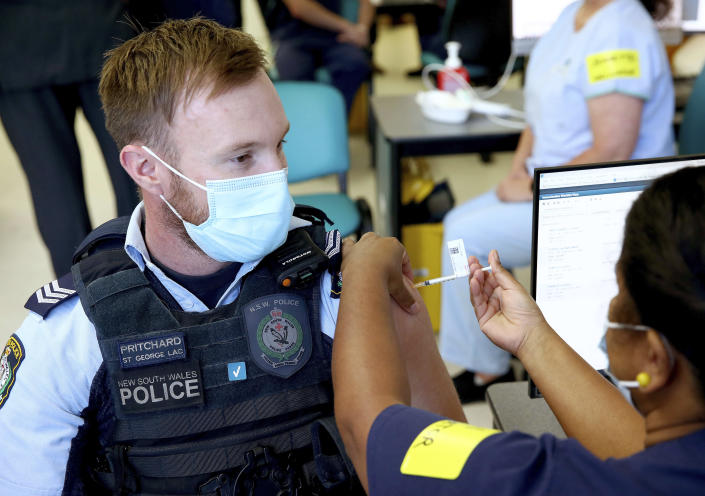 New South Wales Police officer Lachlan Pritchard receives the Pfizer vaccine at the Royal Prince Alfred Hospital Vaccination Hub in Sydney, Australia, Monday, Feb. 22, 2021. Australia has started its COVID-19 vaccination program days after its neighbor New Zealand with both governments deciding their pandemic experiences did not require regulation short cuts. (Toby Zerna/Pool Photo via AP)