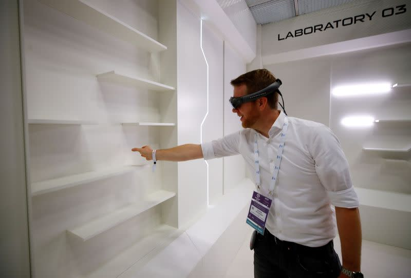 FILE PHOTO: A gamer grabs for a virtual book from an empty shelf as he wears augmented reality goggles during the media day of Europe's leading digital games fair Gamescom, which showcases the latest trends of the computer gaming scene, in Cologne