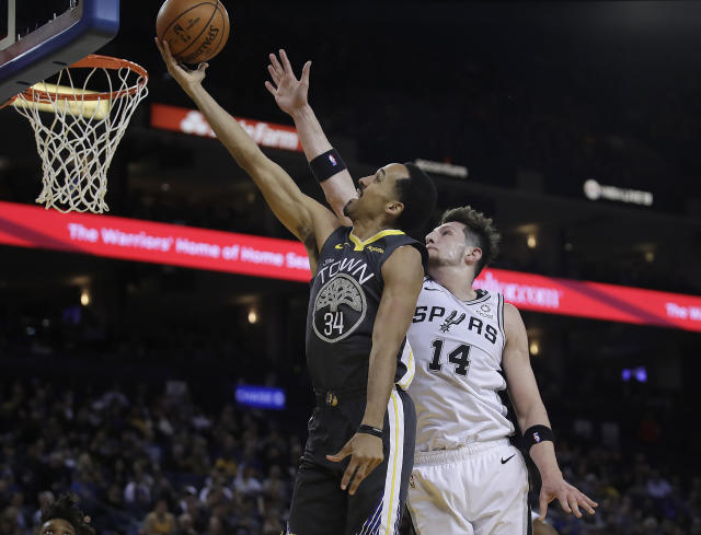 FILE - In this Feb. 6, 2019, file photo, Golden State Warriors' Shaun Livingston, left, lays up a shot past San Antonio Spurs' Drew Eubanks (14) during the second half of an NBA basketball game in Oakland, Calif. Livingston announced his retirement Friday, Sept. 13, 2019, following 15 NBA seasons, an expected move. He reached the NBA Finals in each of his five seasons with Golden State, his ninth NBA team. (AP Photo/Ben Margot, File)