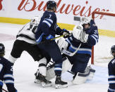 Winnipeg Jets' Dmitry Kulikov (7) gets his stick caught on the jersey of goaltender Connor Hellebuyck as he defends against Los Angeles Kings' Michael Amadio (10) during the first period of an NHL hockey game Tuesday, Oct. 22, 2019, in Winnipeg, Manitoba. (Fred Greenslade/The Canadian Press via AP)
