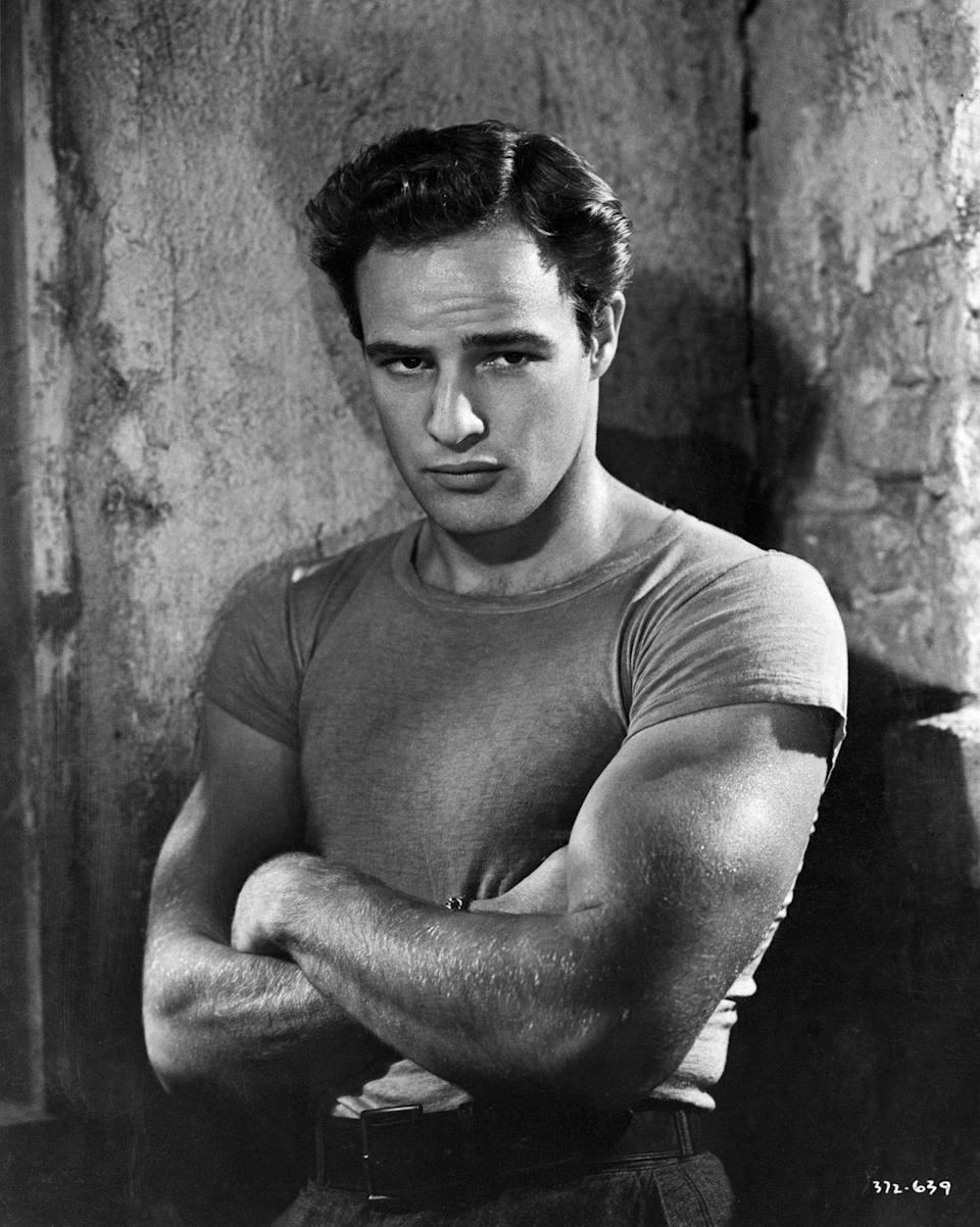 <p>The original guy's guy and king of flex was none other than Oscar-winning actor Marlon Brando. Here, he subtly crosses his arms (aka flexes) on the set of <em>A Streetcar Named Desire.</em></p>