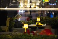 A woman, wearing a face mask to protect against coronavirus enjoys a warm evening sitting at a street-side cafe in the center of Moscow, Russia, Friday, Sept. 25, 2020. Moscow authorities have issued a recommendation for the elderly to stay at home and for employers to allow as many people as possible to work remotely, following a rapid growth of the coronavirus caseload in the Russian capital. (AP Photo/Alexander Zemlianichenko)
