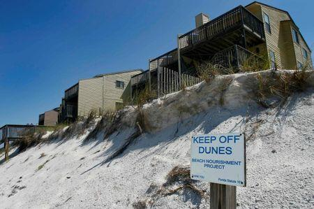 A sign warns beach goers to stay off the frontal dune in front of older properties built on the Gulf Coast at Cape San Blas, south of Port St. Joe, Florida, June 29, 2014. FLORIDA REUTERS/Phil Sears