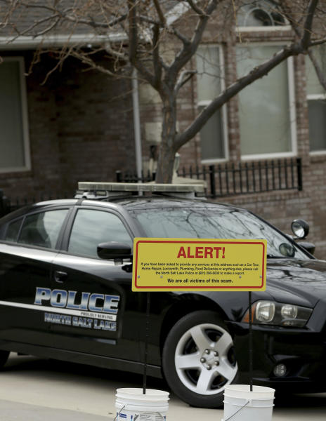 A warning sign and a police officer's vehicle are stationed at Walt Gilmore's home on Thursday, March 21, 2019. The Utah family has become the victim of extreme stalking involving unwanted service providers repeatedly being sent to their home, according to the homeowner and police. (Laura Seitz/The Deseret News via AP)