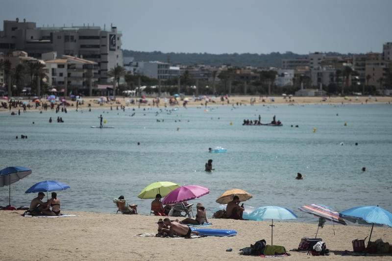 Sunbathers enjoy the beach in the Balearic Islands capital of Palma de Mallorca, Spain, Wednesday, July 29, 2020. Concerns over a new wave of coronavirus infections brought on by returning vacationers are wreaking havoc across Spain's tourism industry, particularly in the Balearic Islands following Britain's effective ban on travel to the country. (AP Photo/Joan Mateu