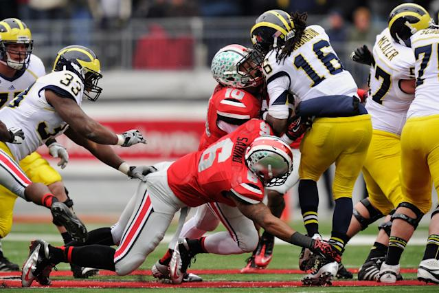 COLUMBUS, OH - NOVEMBER 24: Etienne Sabino #6 and Ryan Shazier #10 of the Ohio State Buckeyes stop Denard Robinson #16 of the Michigan Wolverines short of the first down on a fourth down and two yards to go in the third quarter at Ohio Stadium on November 24, 2012 in Columbus, Ohio. Ohio State defeated Michigan 26-21. (Photo by Jamie Sabau/Getty Images)