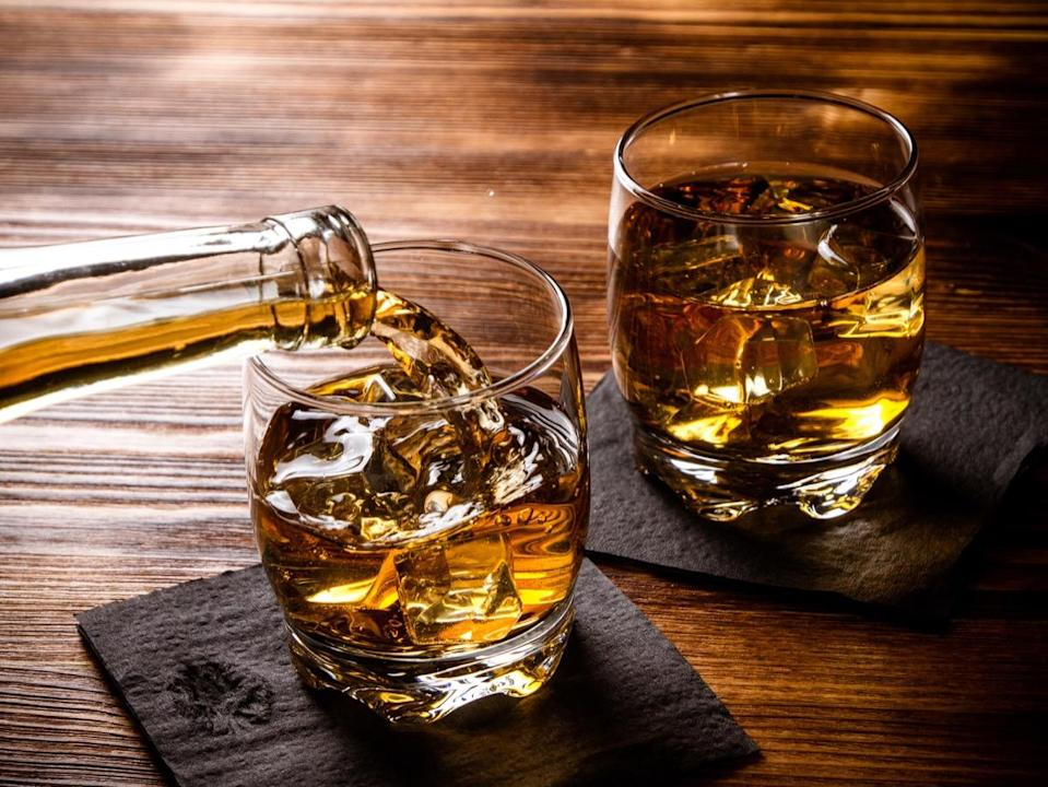 Two glasses of whiskey, one being filled from a bottle