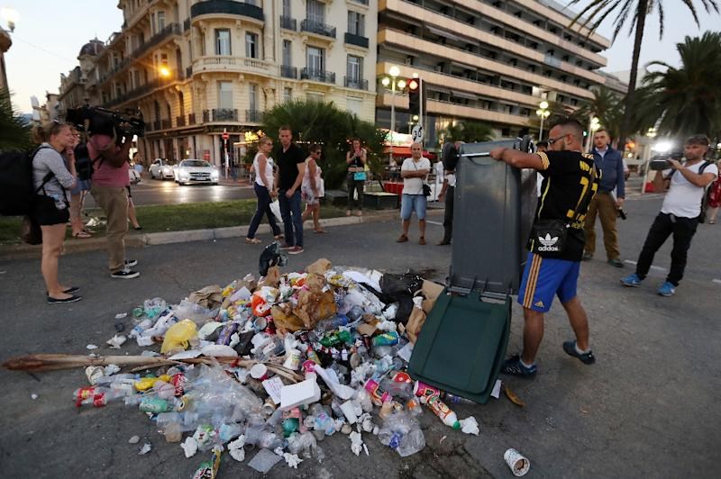 A man empties a rubbish bin on July 18, 2016 on the Promenade des Anglais seafront in Nice, the site where a Tunisian drove a truck into a crowd killing 84 (AFP Photo/Valery Hache)