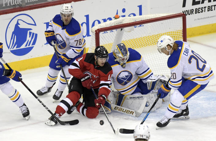 New Jersey Devils left wing Andreas Johnsson (11) attempts to get his stick on the puck as Buffalo Sabres goaltender Linus Ullmark (35) and center Cody Eakin (20) defend during the first period of an NHL hockey game Tuesday, Feb. 23, 2021, in Newark, N.J. (AP Photo/Bill Kostroun)