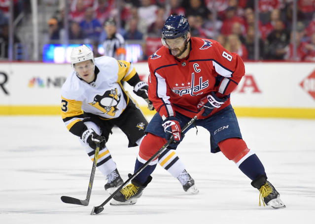 Washington Capitals left wing Alex Ovechkin (8), of Russia, skates with the puck in front of Pittsburgh Penguins defenseman Olli Maatta (3) during the first period in Game 2 of an NHL second-round hockey playoff series, Sunday, April 29, 2018, in Washington. (AP Photo/Nick Wass)