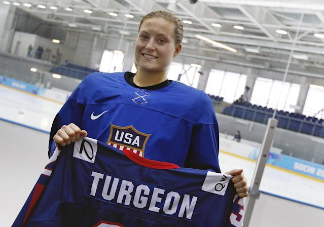 """Lyndsey Fry holds up the hockey jersey Tuesday, Feb. 11, 2014 in Sochi, Russia that belonged to her friend Liz Turgeon that she hand carried in her luggage to the 2014 Winter Olympics. Despondent over the death of Turgeon in a car accident, Fry nearly played herself out of contention for a spot on the U.S. women's hockey team that was soon to be selected for the Sochi Olympics. Two years later she found motivation in her sorrow, telling her parents, """"I'm going for it,"""" and rededicating herself to the sport that she and Turgeon shared. (AP Photo/Petr David Josek)"""