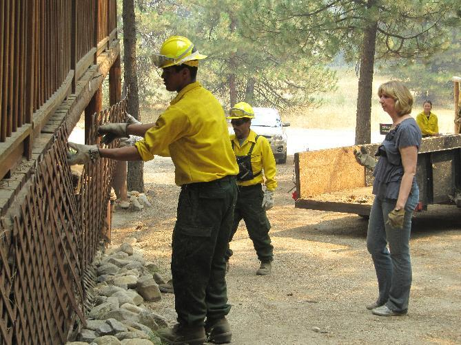 Denise Freeman, right, looks on as firefighters remove the wooden lattice on the side of her log home in Featherville, Idaho on Wednesday, Aug. 15, 2012. Freeman was among residents warned that they will likely have to evacuate their homes because of a nearby wildfire burning on 100 square miles, less than five miles from Featherville. (AP Photo/Jessie L. Bonner)