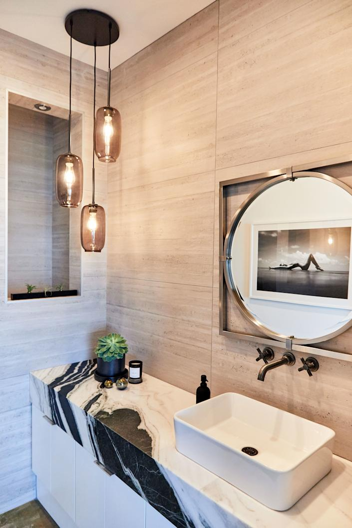 "Huston chose black-and-white marble for the powder room, with cement tile for the walls and an exotic black-and-white photograph, also by Harry Mark; ""I thought fit pretty good in there,"" he says."