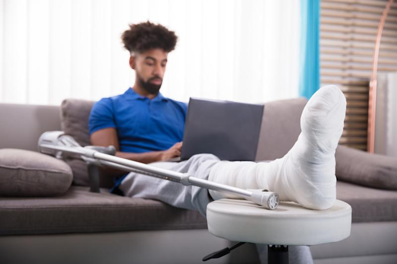 Man sitting on couch with his leg wrapped and propped up, a crutch next to him.