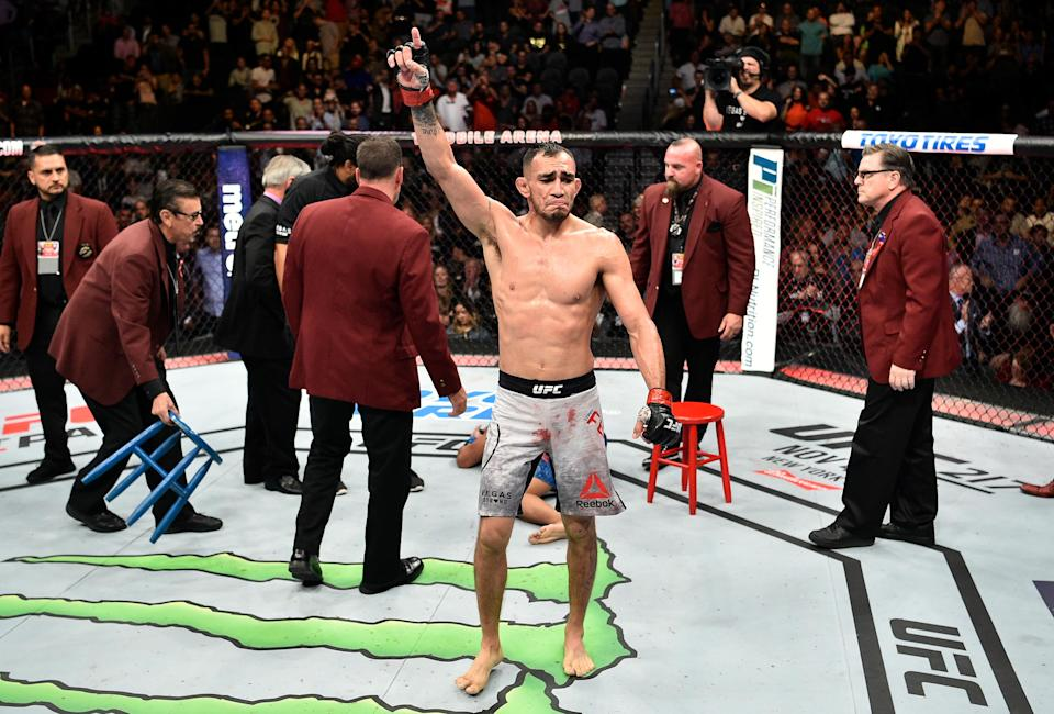 Tony Ferguson (center) celebrates after submitting Kevin Lee to win the UFC interim lightweight title. (Getty)