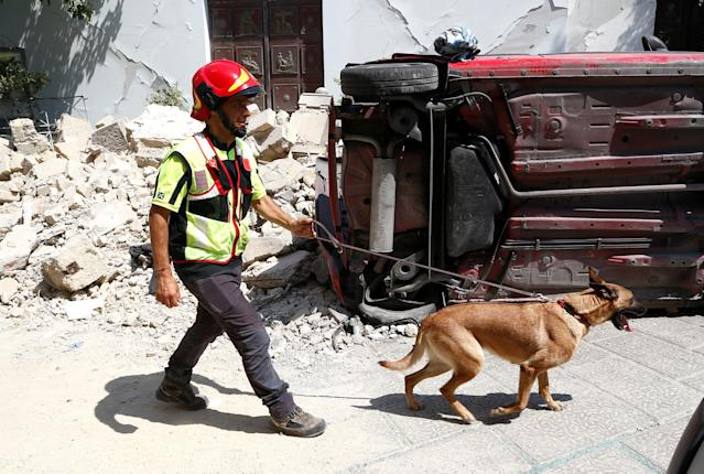<p>A rescue worker inspects with a dog the damaged area after an earthquake hits the island of Ischia, off the coast of Naples, Italy, Aug. 22, 2017. (Photo: Ciro De Luca/Reuters) </p>